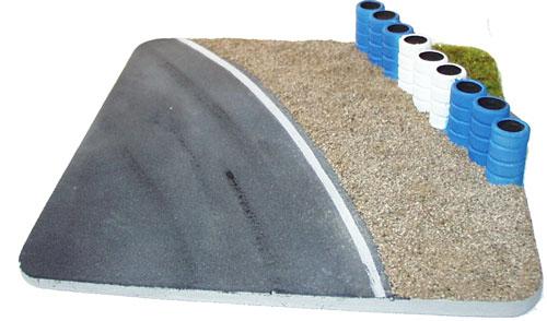 Kurve mit Kiesbett und Reifenstapel blau/weiß